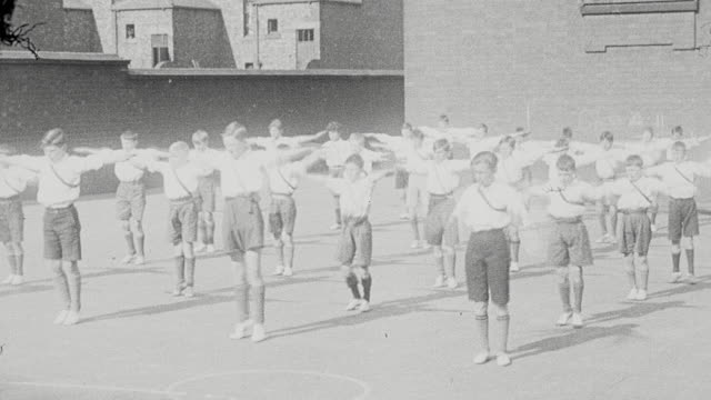 1925 ws group of schoolboys performing calisthenics, including leap frog and scotch the snake, outdoors on playground / newcastle upon tyne, england, united kingdom - schoolboy stock videos and b-roll footage