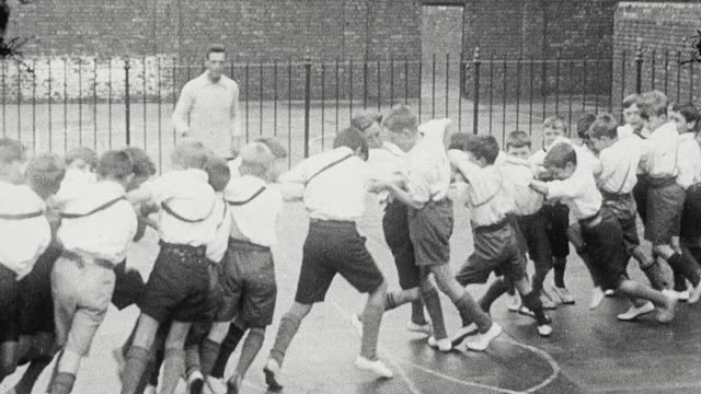 1925 montage group of schoolboys performing calisthenics including relay racing and tug o' war outdoors on playground / newcastle upon tyne, england, united kingdom - 1925 stock videos & royalty-free footage