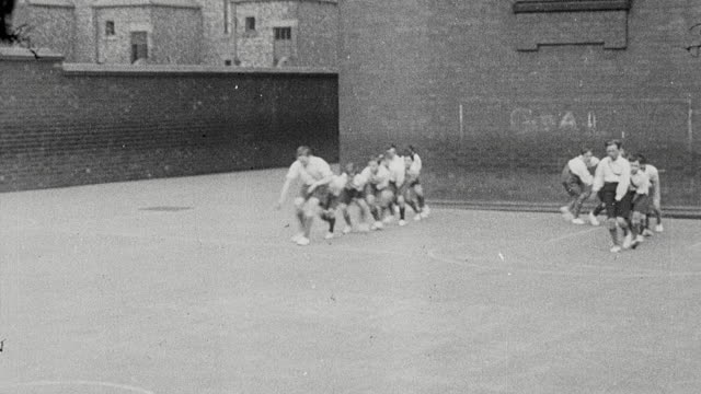 1925 ws group of schoolboys performing calisthenics outdoors on playground / newcastle upon tyne, england, united kingdom - 1925 stock videos & royalty-free footage