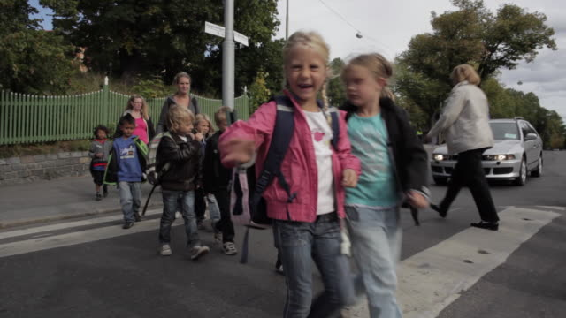ws group of schoolchildren crossing street / stockholm, sweden - svezia video stock e b–roll