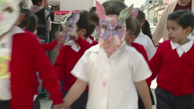 MS CU Group of schoolchildren wearing masks walking on street / Oaxaca, Mexico