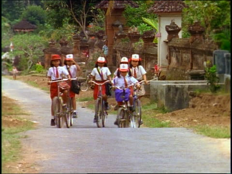 group of schoolgirls in uniform riding bicycles on country road towards camera / bali - malaysian ethnicity stock videos & royalty-free footage