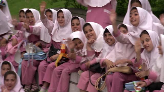vidéos et rushes de ms pan group of schoolgirls sitting outdoors, iran - iran