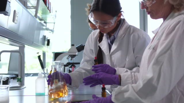 group of scientists performing experiments in the laboratory - chemistry stock videos & royalty-free footage