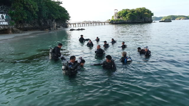 group of scuba divers preparing for dive at hundred islands national park in alaminos, ilocos region, philippines, on friday, september 25, 2020. - aqualung diving equipment stock videos & royalty-free footage