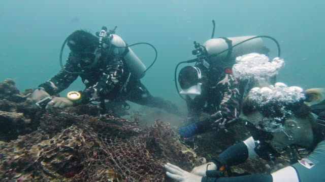 group of scuba divers volunteering with marine reserve rangers on underwater environmental pollution cleanup - fishing net stock videos & royalty-free footage
