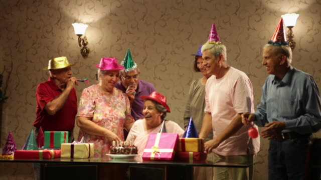 stockvideo's en b-roll-footage met group of senior people celebrating birthday party  - feestmuts