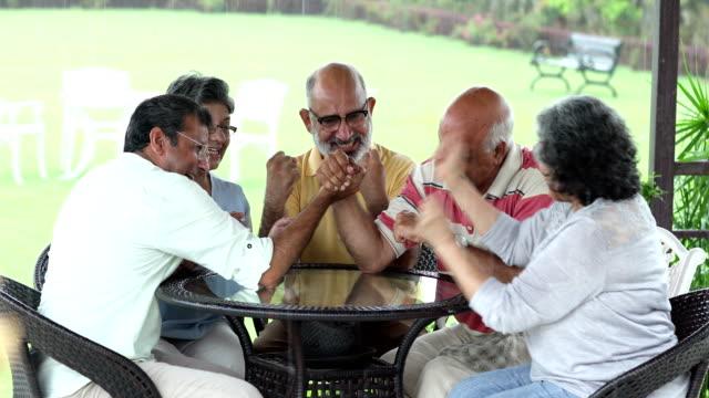 group of senior people enjoying at home, delhi, india - armdrücken stock-videos und b-roll-filmmaterial