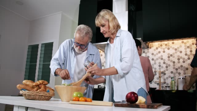 group of senior social gathering around kitchen counter at home - kitchenware department stock videos and b-roll footage