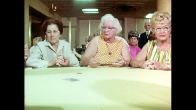 vidéos et rushes de group of senior women play poker around table; 1969 - poker