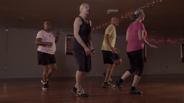 vídeos de stock, filmes e b-roll de a group of seniors coordinate their moves in a zumba class. - coordenação