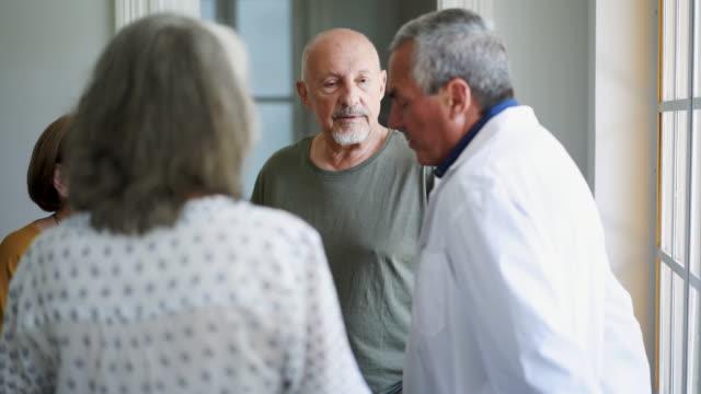 vidéos et rushes de groupe de personnes âgées parlant à leur docteur dans la maison de repos - vêtements professionnels hospitaliers