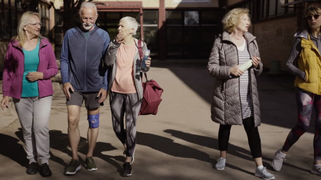 group of seniors walking away from community center - body positive stock videos & royalty-free footage
