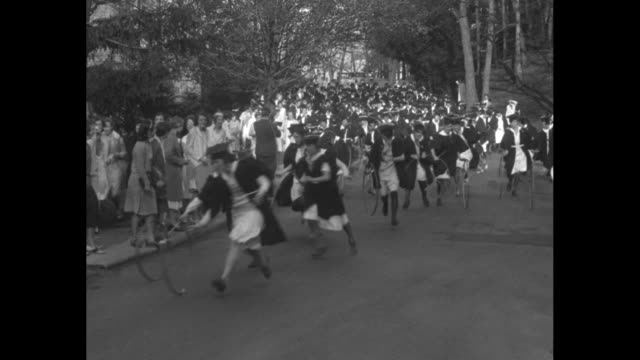 group of seniors wearing caps and gowns ready with hoops to start race / they race down street past camera rolling hoops, students on sidewalk... - 1930 stock videos & royalty-free footage