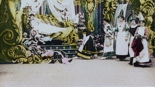 vídeos de stock e filmes b-roll de 1903 ws group of servants helping a queen get dressed and into bed and then she is carried off by a group of men during the film illusions, le royaume des fées (the kingdom of fairies) by georges melies - 1903
