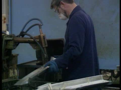 man working on metal panel gv factory floor with articles on hoists - hochziehen stock-videos und b-roll-filmmaterial