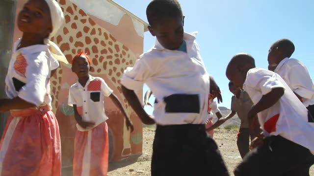 vidéos et rushes de ms group of several children dancing and singing in uniform audio / bergsig, kunene, namibia - afrique