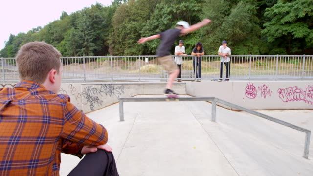 ms group of skateboarders watching friend ride in skate park - railings bildbanksvideor och videomaterial från bakom kulisserna
