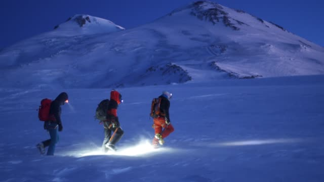 vidéos et rushes de group of skiers hiking through a wintery mountainside at dawn near mount elbrus - lampe frontale