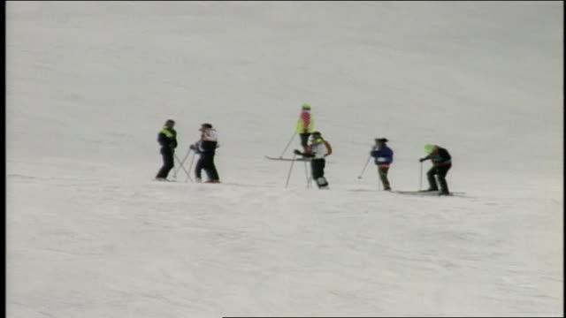 cu group of skiers in neon coats to wide shot of busy skiing mountain in butte colorado - スキーウェア点の映像素材/bロール
