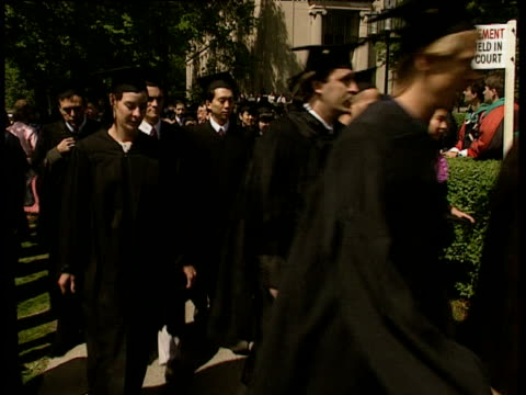 group of slightly nervous looking graduates wearing graduation gowns and mortarboards walk past camera. - graduation stock videos and b-roll footage