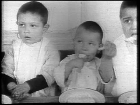 pan group of small boys eating at table during famine / russia / newsreel - 1921 stock videos & royalty-free footage