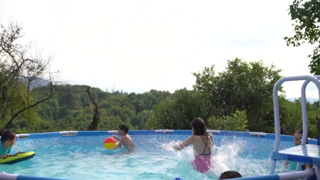 group of small children in swimming pool in the garden of their country house - swimming shorts stock videos & royalty-free footage