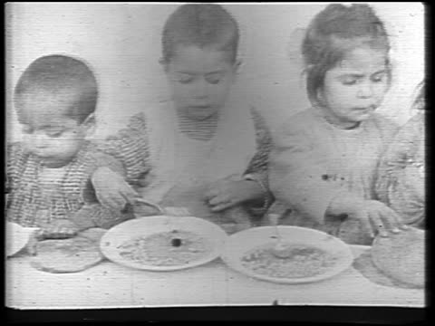 stockvideo's en b-roll-footage met pan group of small girls eating at table during famine / russia / newsreel - 1921