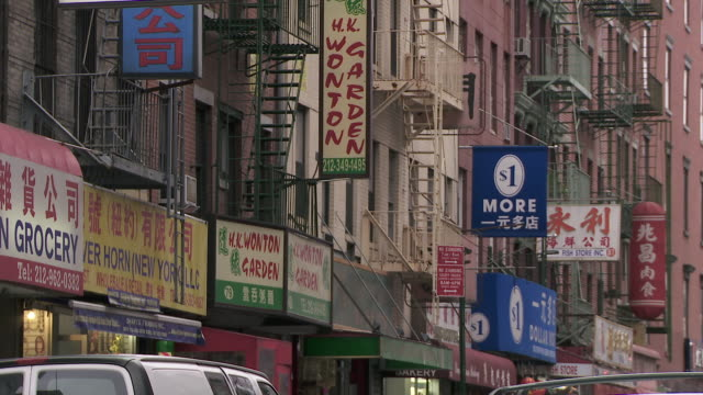 a group of small store fronts on mulberry street in chinatown.  grocery, restaurants, and retail shops - chinatown stock videos and b-roll footage