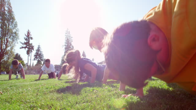 vídeos y material grabado en eventos de stock de ms group of smiling and laughing kids doing push ups during athletics class on grass field next to school - flexiones