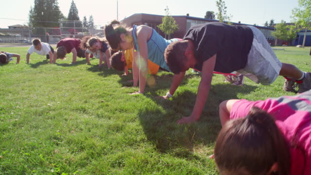 ms group of smiling kids doing push ups during athletics class on grass field next to school - bodyweight training stock videos & royalty-free footage