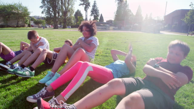 MS Group of smiling kids doing sit ups during athletics class on grass field next to school