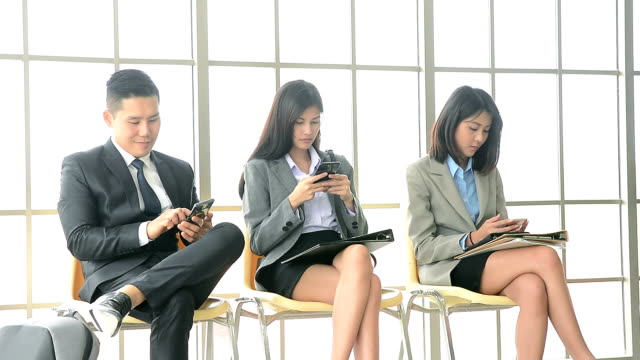 Group of smiling young applicants using smartphone during waiting for called job interview in modern office.