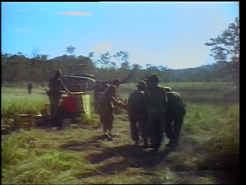 vidéos et rushes de view group of soldiers carrying wounded soldier toward helicopter in field / vietnam - plaie