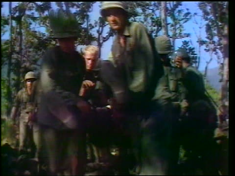1965 group of soldiers carrying wounded soldier with IV drip / others helping wounded to walk