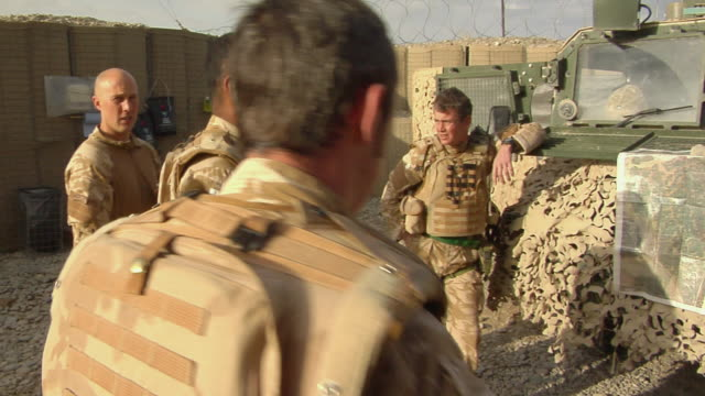group of soldiers having discussion / mausa qala, helmand province, afghanistan. - british military stock-videos und b-roll-filmmaterial