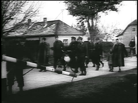 B/W 1956 group of soldiers others walk thru border gate from Hungary to Austria during revolution
