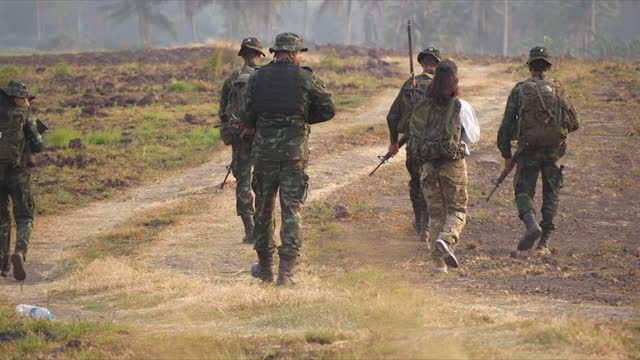 group of soldiers walking in the maneuver. silhouette soldiers in uniforms and weapons. - army soldier stock videos & royalty-free footage