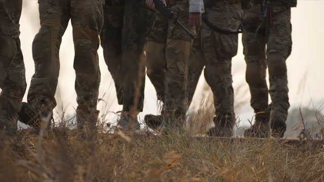 group of soldiers walking in the maneuver. silhouette soldiers in uniforms and weapons. - army stock videos & royalty-free footage