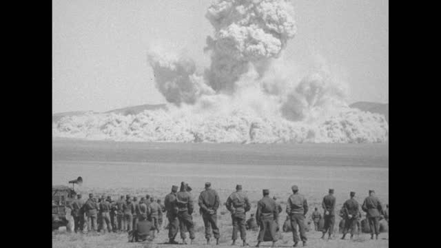 """group of soldiers watching huge cloud of dirt and dust hanging in air from explosion / close shot of sign reading """"us atomic energy commission,... - atomo video stock e b–roll"""