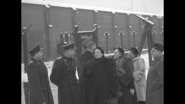 stockvideo's en b-roll-footage met group of soviet officers us officers and women standing in front of prison / shot of snow on ground / closer view of group sign behind them reading... - optocht