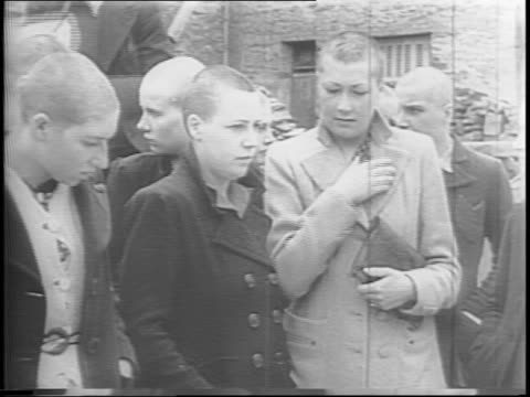a group of spectators watch as a man cuts the hair off of a woman accused of helping the nazis / women cover their faces / montage of woman getting... - la manche stock videos and b-roll footage