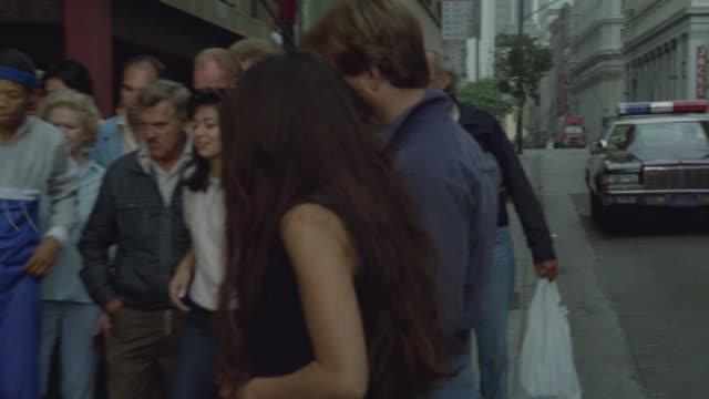group of spectators watching breakdancers on a sidewalk. - cassetta video stock e b–roll