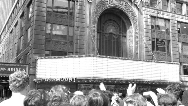 a group of spectators waves toward the paramount theater. - broadway manhattan stock-videos und b-roll-filmmaterial