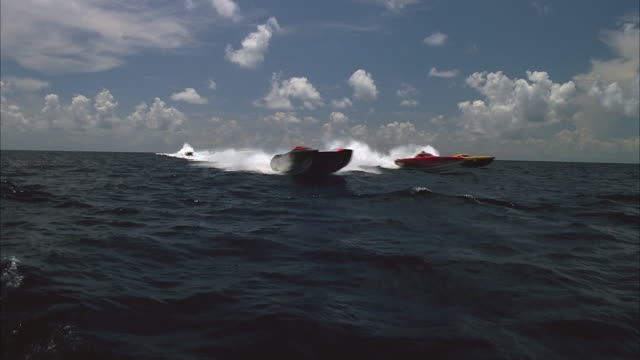 sm ws group of speedboats coming across horizon, splashing camera as they move past it/ miami, florida - moving past stock videos & royalty-free footage