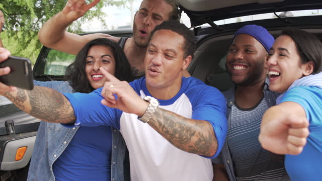 group of sports fans cheering for selfie at tailgating party - five people stock videos & royalty-free footage