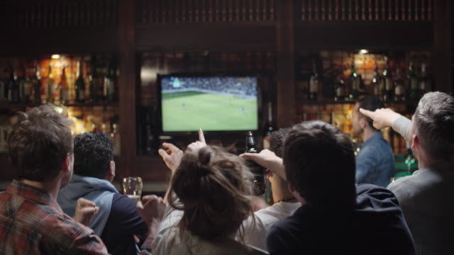 group of sports fans watching soccer in pub - bar video stock e b–roll