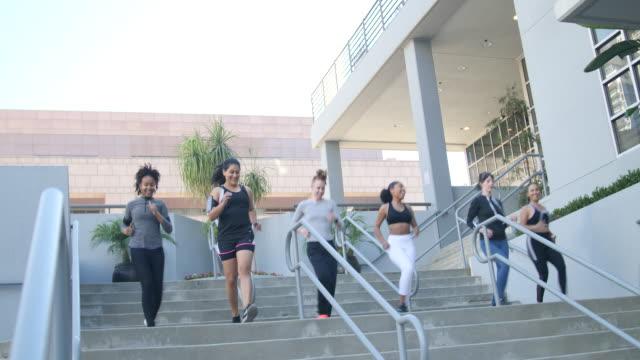 階段を駆け下りるスポーティな女性のグループ - staircase点の映像素材/bロール