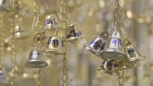 group of strings hanging the small silver and golden bells with bokeh in background. - group of objects stock videos & royalty-free footage