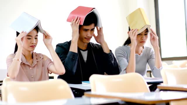 gruppe von studenten mit buch auf dem kopf . zurück zum schulkonzept. - kopf stock-videos und b-roll-filmmaterial